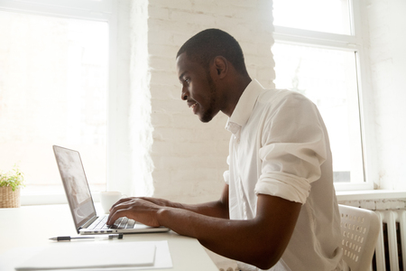 African businessman working on laptop sitting at home office desk, happy black intern employee looking at computer screen typing or browsing web, using software application for business and education Stock Photo