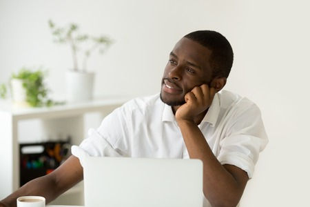 Dreamy african american young man thinking of new idea at workplace, black lazy worker avoiding work lost in thoughts, absent-minded intern dreaming of successful business and happy future career