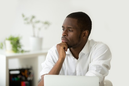 Young african-american thoughtful businessman holding hand on chin planning future project at work with laptop, black meditative african entrepreneur thinking of new idea for business improvement Stok Fotoğraf