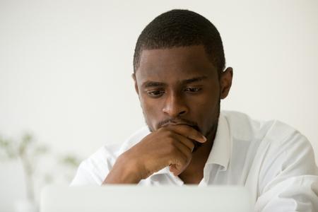 Fokussierter Afroamerikanermanager, der an dem Laptop schwer denkt an Problemlösung, der konzentrierte schwarze Geschäftsmann arbeitet, der über Arbeitsaufgabe, beschäftigter ernster Angestellter online trifft Entscheidung, Headshot betroffen ist