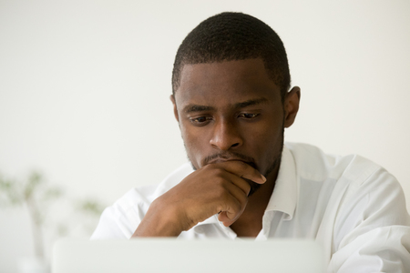 Skoncentrowany menedżer afroamerykański pracujący na laptopie ciężko myślący o rozwiązaniu problemu, skoncentrowany czarny biznesmen zaniepokojony zadaniem w pracy, zajęty poważnym pracownikiem podejmującym decyzje online, strzał w głowę