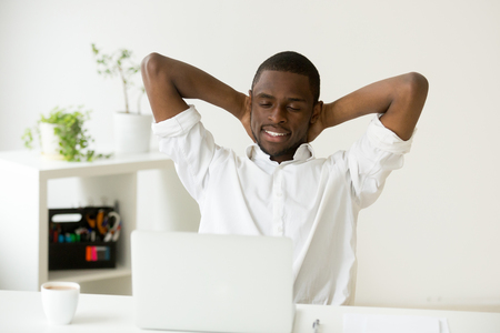 Satisfied happy attractive african american man relaxing hands behind head with coffee and laptop having break at home office desk, black relaxed businessman enjoying pleasant good morning at work