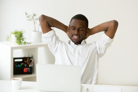 커피와 노트북 집 사무실 책상에서 휴식을 갖는 머리 뒤에 손을 편안하게 만족 행복 매력적인 흑인 남자, 직장에서 즐거운 좋은 아침을 즐기는 검은 편안한 사업가
