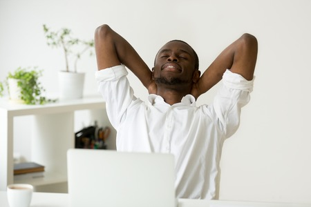African american young businessman relaxing at workplace with laptop, relaxed calm black employee feels happy at work breathing fresh air, smiling man enjoys break stretching in office, peace of mind Standard-Bild