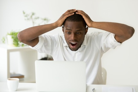 Amazed excited african-american man surprised by unexpected good news win result online, astonished black businessman looking at laptop screen with wow face wonders unbelievable fantastic email offer