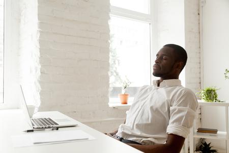 ノートパソコンでホームオフィスのデスクに座って新鮮な空気を吸って仕事の後にリラックスしたアフリカ系アメリカ人の男性、職場での生産性を