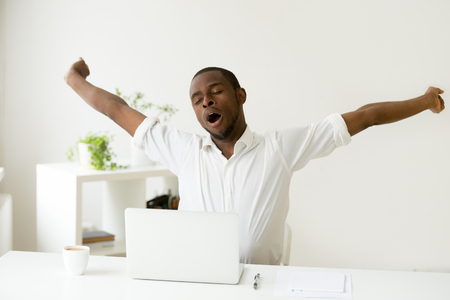 Sleepy african american man stretching yawning at workplace, tired black lazy worker feels lack of sleep fatigue taking rest for relaxing morning coffee break sitting at home office desk with laptop
