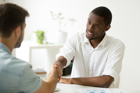 African american businessman handshaking caucasian partner making deal, black financial advisor consultant greeting client sitting at office desk, diverse entrepreneurs shaking hands starting meeting Stock Photo