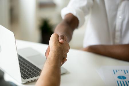 Wielorasowa koncepcja biznesowego uścisku dłoni, partnerzy afroamerykańscy i kaukascy ściskający ręce nad biurkiem, różni biznesmeni zgadzają się, aby umowa była satysfakcjonująca z wyniku negocjacji, widok z bliska