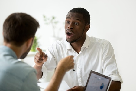 African american businessman disagreeing arguing debating during office negotiations, black negotiator disputing with caucasian partner, insisting on point of view in discussion, explaining opinion