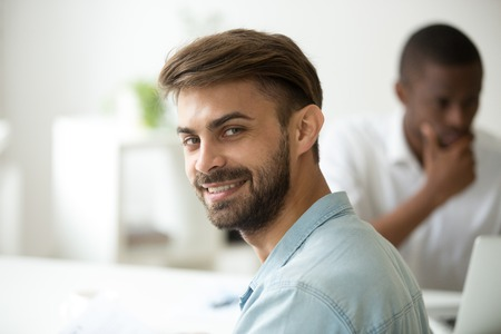 Smiling young caucasian entrepreneur, ambitious intern or successful professional looking at camera working with african colleague in office, happy white job applicant at interview, headshot portrait