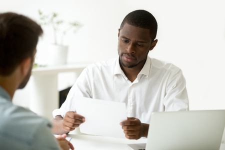Serious african businessman reading document at meeting, black entrepreneur considering contract, company ceo analyzing report, hr manager or employer holding applicants cv resume at job interview 版權商用圖片