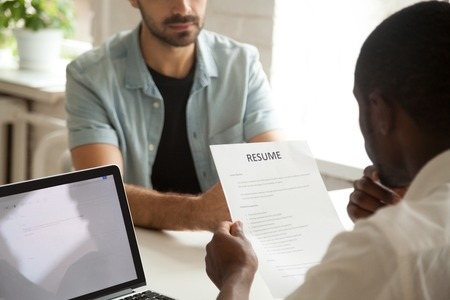 African american hr manager holding applicants curriculum vitae at job interview, black recruiter or employer considering cv of caucasian vacancy candidate during hiring negotiations, focus on resume Stockfoto - 95223670