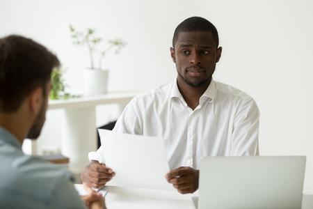 El gerente de recursos humanos afroamericano parece dudoso sobre la contratación de un candidato incompetente, un empleador negro incierto y desconfiado escéptico sobre el cv solicitante, un currículum vitae fallido concepto de rendimiento de entrevista de trabajo