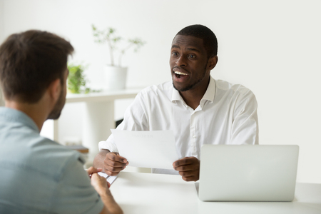 Good first impression at job interview concept, excited african hr manager impressed by career achievements in resume of caucasian candidate, black employer amazed by accomplishments in applicants cv