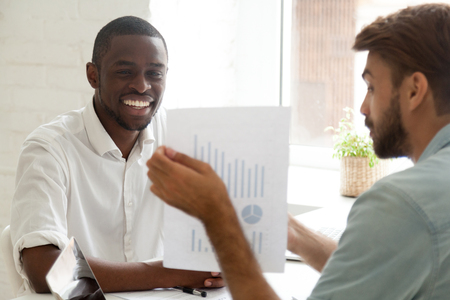 Caucasian advisor consulting african american client about loan, mortgage or insurance showing financial statistics, white adviser talking to black smiling businessman about new project investment