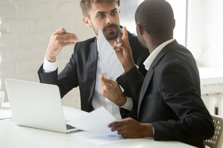 Multiracial african and caucasian partners arguing about contract fraud, dissatisfied diverse businessmen having conflict disagree with terms, breaking agreement rejecting unacceptable conditions