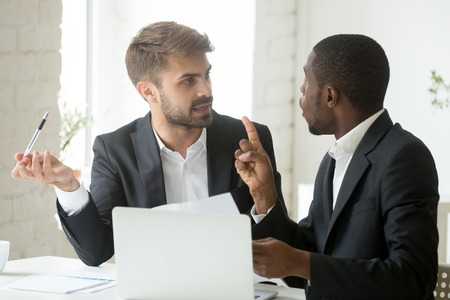 African black client having claims about business document disagreeing with caucasian partner, stressed diverse businessmen arguing in office disgruntled by bad contract or obligations noncompliance Imagens