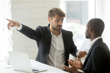 Angry rude caucasian executive firing male incompetent african employee for bad work, impolite white partner telling black businessman to get out detecting fraud, prejudice and racial discrimination