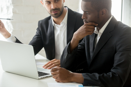 Serious black businessman thinking over business offer looking at laptop while caucasian partner explains deal details, successful african investor in suit considering investment listening to advisor