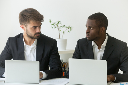 Multiracial office rivals looking at each other with hate envy sitting with laptops, corporate competitors african and caucasian employees compete in business work, team rivalry at workplace concept