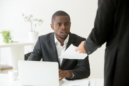 Uomo d'affari africano scioccato sorpreso che riceve un avviso di licenziamento inaspettato dal collega capo caucasico, impiegato nero stupito dalla notifica di debiti o lettere con cattive notizie, licenziato