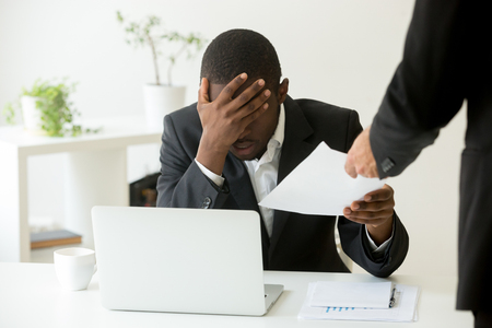 Frustrated upset african american office employee receiving dismissal notice at workplace, depressed bankrupt black entrepreneur getting fired from work, distraught by notification warning about debt Stock Photo