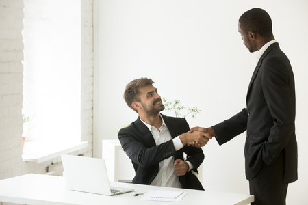 African american boss congratulating caucasian employee with promotion shaking hands, black executive appreciating office worker for good work result by handshake, motivation and recognition concept