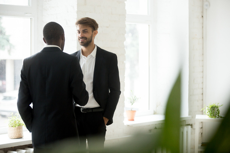 Diverse successful businessmen standing talking in office, friendly african american and caucasian colleagues in suits discussing project idea at work, company executives having pleasant conversation 写真素材 - 95338374