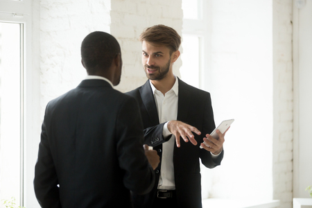 Multiracial businessmen discuss new idea with tablet at coffee break, two diverse colleagues talk about work, caucasian entrepreneur explains african american colleague project app using gadget