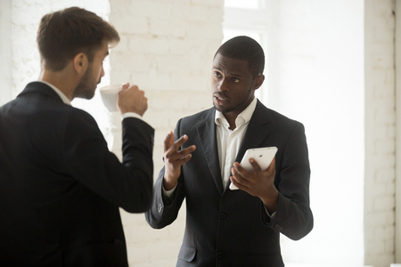 African american businessman discussing new app with caucasian partner holding digital tablet, diverse office workers or multiracial executive team talking during coffee break using business gadget