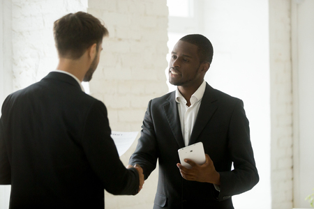 Diverse business partners in suits shaking hands standing in office, smiling african american entrepreneur holding digital tablet handshaking caucasian businessman after signing contract making deal