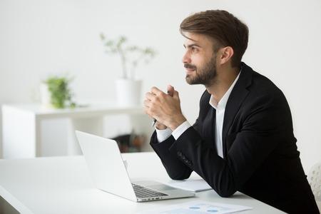 ビジネスビジョンの見通しを考えるスーツの若い夢のようなビジネスマンは、ラップトップと仕事で将来のプロジェクトのアイデアを計画し、成功 写真素材