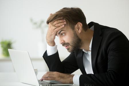Worried stressed businessman in suit shocked by bad news using laptop at work, desperate bankrupt investor lost money online depressed by financial problem debt, frustrated worker tired of overwork