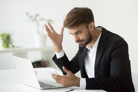 Angry businessman stressed about smartphone problem at workplace, frustrated executive feeling indignant annoyed about phone call, broken not working cell, received spam bad news in mobile message 版權商用圖片