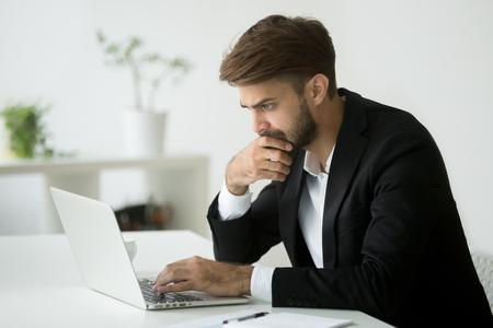 オンラインニュースを読んだり、画面を見てラップトップで働くビジネス上の問題を解決するスーツに焦点を当てた深刻なビジネスマンは、コンピ