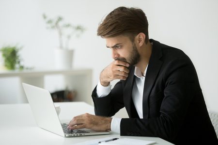 Focused serious businessman in suit thinking reading online news or solving business problem working on laptop looking at screen, worried puzzled executive managing stock market risks using computer Imagens - 95287781