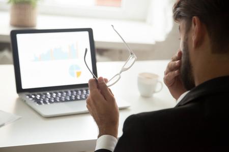 Cansado de que el empresario informático se quite los anteojos sintiendo fatiga visual frente a la computadora portátil, el empleado tiene problemas de visión y visión, fatiga ocular y concepto de exceso de trabajo, vista posterior sobre el hombro Foto de archivo