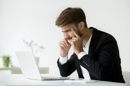 Der müde Geschäftsmann, der die Augen betrachten den Laptopschirm schielt, der versucht, sich zu konzentrieren, der Büroangestellte, der an das on-line-Problem leidet unter Ermüdung, Kopfschmerzen oder schlechtem Anblick, Computersyndrom denkt