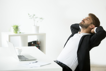 Successful young businessman in suit relaxing at workplace with laptop finished work, relaxed calm employee feels happy breathing fresh air, smiling ceo enjoys break in office, no stress free relief Banque d'images