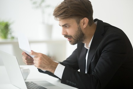 Amazed businessman in suit feeling shocked by reading mail, surprised entrepreneur stunned by unexpected loan rate increase in bank notice, confused employee astonished by unbelievable news in letter Stockfoto - 95324754