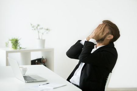 Distraught stressed businessman in suit covers face with hands feeling despair after business failure online sitting at work desk with laptop, frustrated hopeless entrepreneur shocked by bankruptcy Stockfoto - 95313438