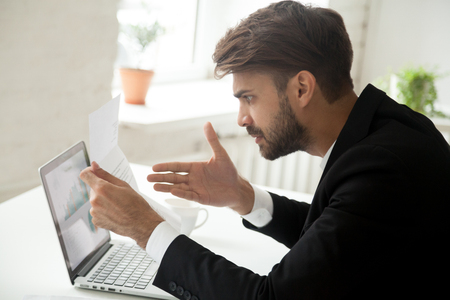 Angry businessman indignant disagree with information in mail business letter, annoyed disgruntled entrepreneur frustrated stressed by high taxes bill or past due unpaid debt, bad financial results Banco de Imagens - 95311213