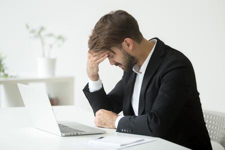 Deprimierter erfolgloser Geschäftsmann glaubt schrecklichen Kopfschmerzen, verstörtes betontes Unternehmerbedauern des Geschäftsfehlers, der durch den Konkurs hoffnungslos nach dem Ausfall entsetzt wird, der am Arbeitsschreibtisch mit Laptop sitzt