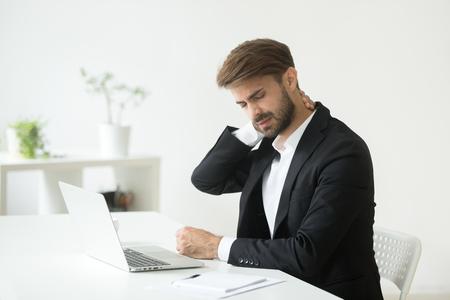 Jonge zakenman in pak voelt nekpijn masseren gespannen spieren na zittend werk zittend op een ongemakkelijke bureaustoel, werknemer met computer syndroom lijdt aan chronische cervicalgia pijn