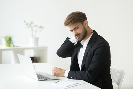 Joven empresario en traje siente dolor de cuello al masajear los músculos tensos después del trabajo sedentario sentado en una silla de oficina incómoda, el empleado con síndrome de computadora sufre de dolor de cervicalgia crónica
