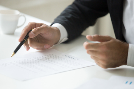 Businessman offering to sign business contract concept, promising good deal convincing to put signature, negotiating pointing on legal document terms, proposing partnership insurance, close up view