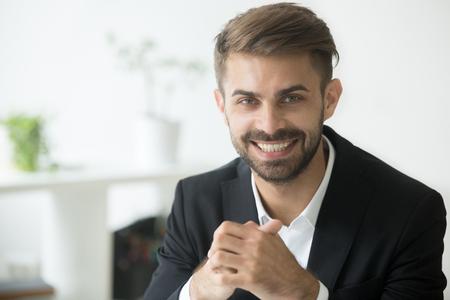 カメラを見てスーツを着て笑顔の魅力的な若いミレニアルのビジネスマン、楽観的な陽気なコーチ、幸せな野心的なプロマネージャー、販売員やビ