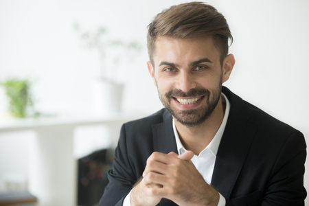Smiling attractive young millennial businessman wearing suit looking at camera, optimistic cheerful coach, happy ambitious professional manager, sales person or business expert head shot portrait Banco de Imagens