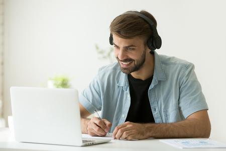 Lächelnder Mann in den Kopfhörern, die das aufpassende Webinar des Bildschirms, Geschäftsvideoanruf machend betrachten, junger Geschäftsmann, der on-line-Schreibensanmerkungen des Fernkunden konsultiert, Stunde, die Abstandsjobinterview hält Standard-Bild